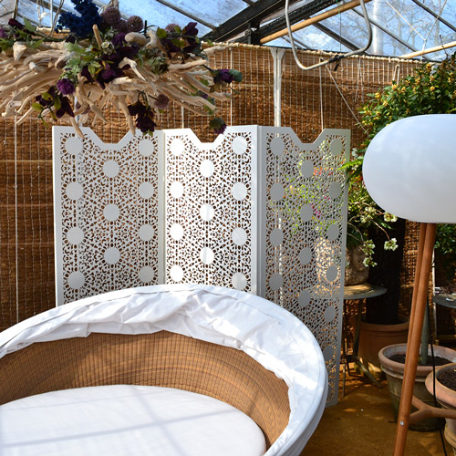 Perforated laser cut metal screens in nottingham lace pattern in garden setting
